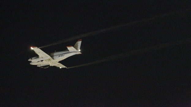 A Beechcraft airplane sprays insecticide over Dallas early Monday morning to curb the spread of West Nile virus. (AP)