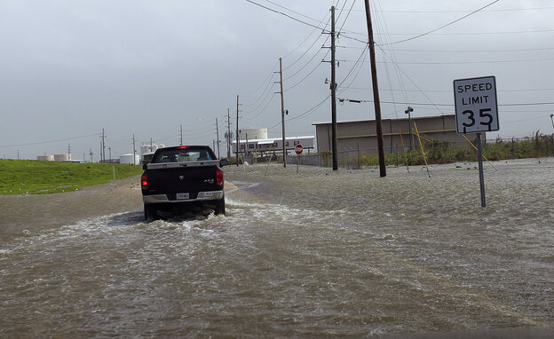 A Plaquemines Parish vehicle rides through rising floodwater behind the levee as Isaac approaches on Tuesday.