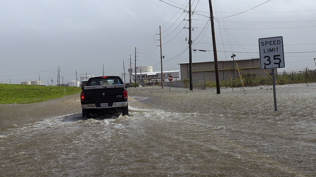A Plaquemines Parish vehicle rides through rising floodwater behind the levee as Isaac approaches on Tuesday. (AP)