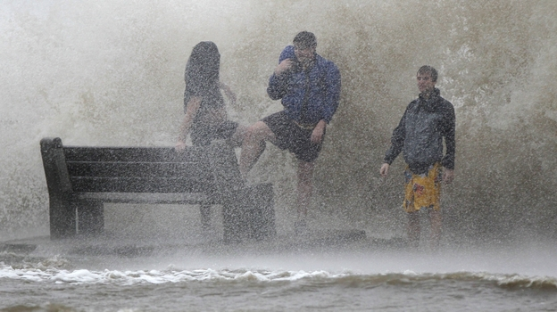 People walk in the storm surge from Hurricane Isaac along Lake Pontchartrain in New Orleans. Isaac was later downgraded to a tropical storm as it continued to grind its way through the Gulf Coast, dropping torrential rain and generating dangerous storm surges. (AP)
