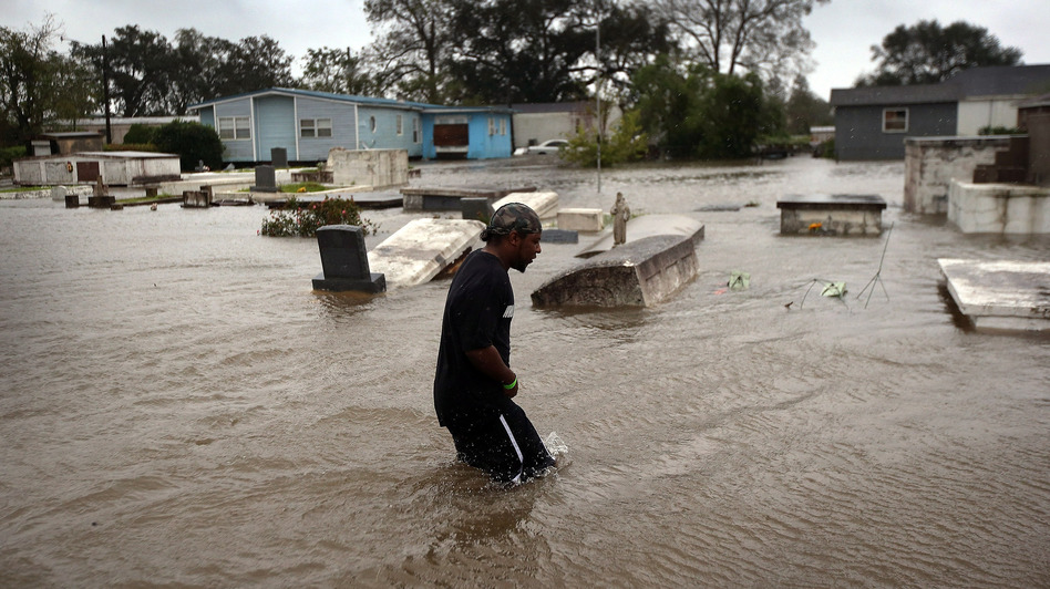 Errol Ragas walks past a cemetery to recover dry blankets from his home as rising waters from Hurricane Isaac flood the neighborhood  of Oakville in Plaquemines Parish, Louisiana. (Getty Images)