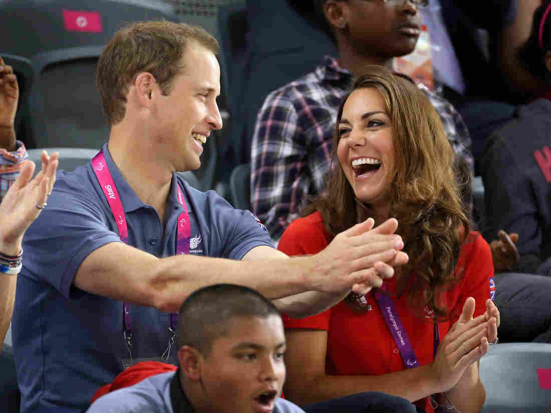 """Prince William, Duke of Cambridge and Catherine, Duchess of Cambridge share a joke as they clap whilst watching the track cycling on day 1 of the London 2012 Paralympic Games. (I left in the part of the original caption that says """"whilst,"""" because, come on.)"""