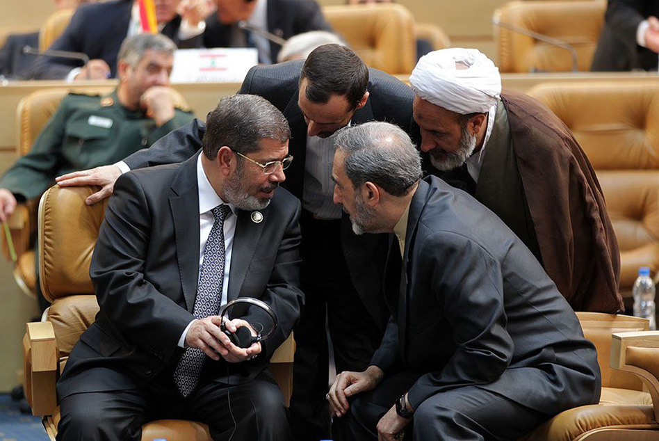 Egyptian President Mohamed Morsi, left, speaks with former Iranian foreign minister Ali Akbar Velayati, right, during the opening of the Nonaligned Movement summit in Tehran.