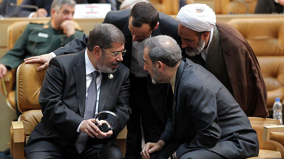 Egyptian President Mohamed Morsi, left, speaks with former Iranian foreign minister Ali Akbar Velayati, right, during the opening of the Nonaligned Movement summit in Tehran. (AFP/Getty Images)