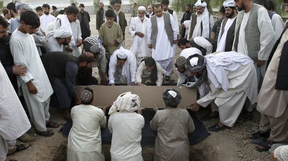 Afghans bury the mayor of  Kandahar, Ghulam Haidar Hamidi, after he was killed in a suicide bombing in July 2011. Afghan officials have extensive security but are still vulnerable to attack. (Reuters via Landov)