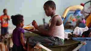 Darrell Hill, 11, feeds his sister Floy Dillon, 2, at a flood shelter in a school gym in Kentwood, La., Thursday. Residents fled to the shelter after officials announced that a dam upstream in Mississippi was in danger of bursting.