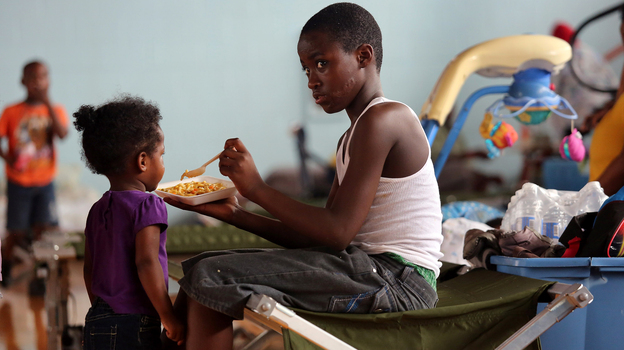 Darrell Hill, 11, feeds his sister Floy Dillon, 2, at a flood shelter in a school gym in Kentwood, La., Thursday. Residents fled to the shelter after officials announced that a dam upstream in Mississippi was in danger of bursting. (Getty Images)