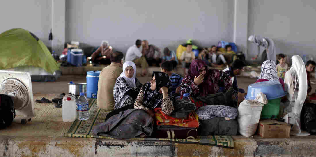 Syrians take refuge Thursday at the Bab Al-Salameh border crossing near the Syrian town of Azaz, in hopes of entering one of the refugee camps in Turkey.
