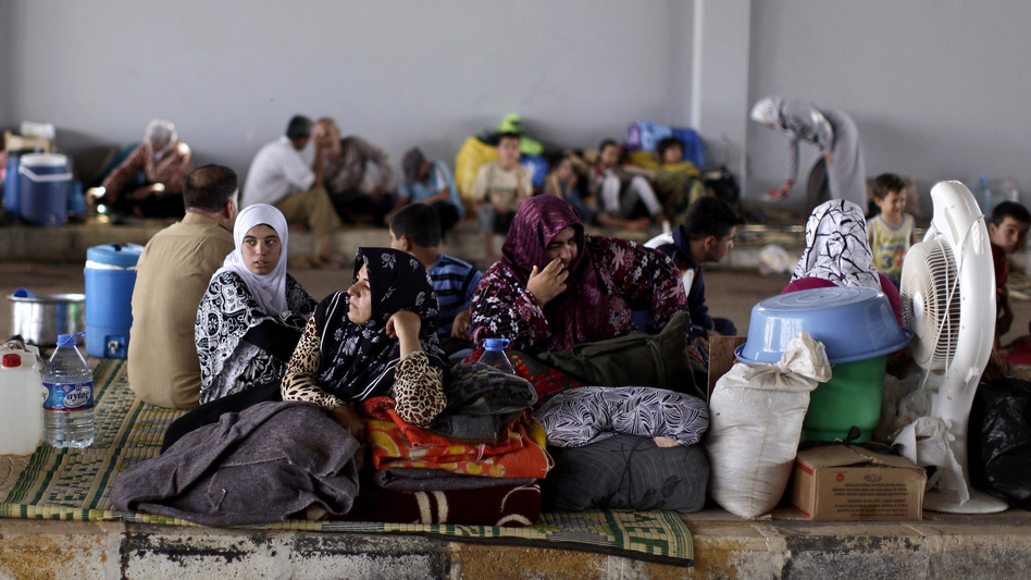 Syrians take refuge Thursday at the Bab Al-Salameh border crossing near the Syrian town of Azaz, in hopes of entering one of the refugee camps in Turkey. (AP)