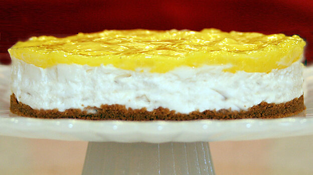 A Lemon Icebox Cheesecake on a cake stand