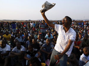 A mine worker sings and dances during a gathering at the Lonmin Platinum Mine near Rustenburg, South Africa, on Wednesday. Some 270 miners were charged with murder Thursday in co