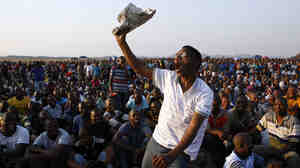 A mine worker sings and dances during a gathering at the Lonmin Platinum Mine near Rustenburg, South Africa, on Wednesday. Some 270 miners were charged with murder Thursday in connection with the  deaths of 34 of their striking colleagues.