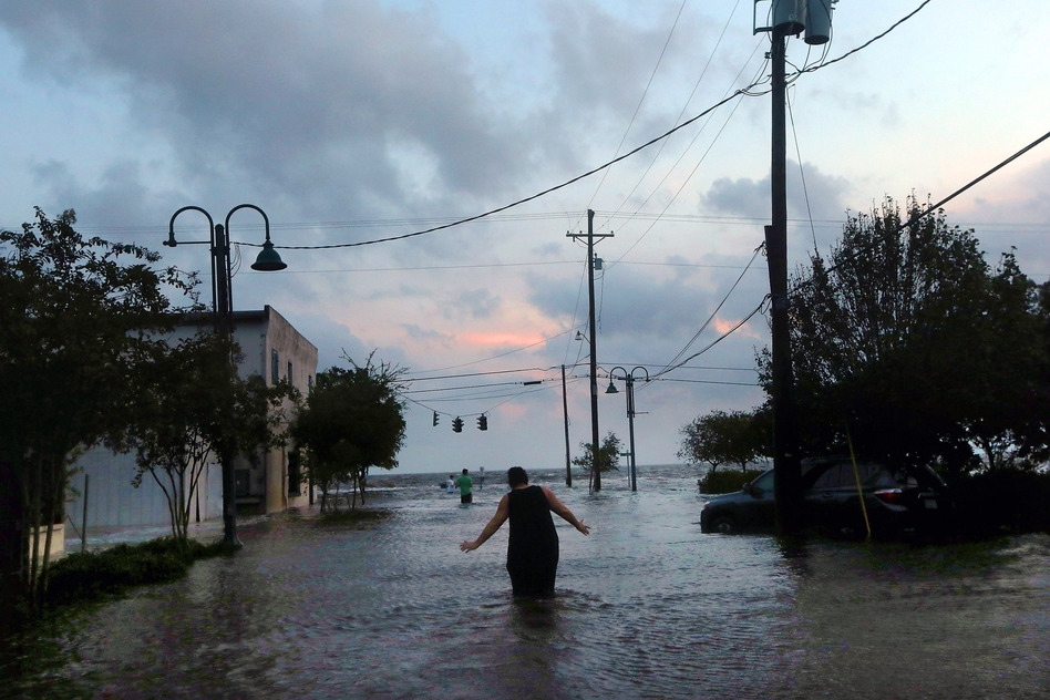 A woman walks through flood waters from Hurricane Isaac's storm surge on the north shore of Lake Pontchartrain Thursday.