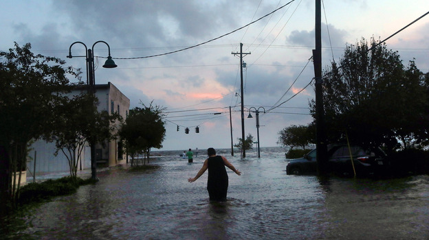A woman walks through flood waters from Hurricane Isaac's storm surge on the north shore of Lake Pontchartrain Thursday. (Getty Images)