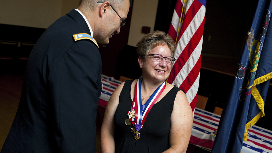 Retired Army Maj. Michelle Dyarman, shown with Lt. Col. William McDonough, smiles after receiving a Purple Heart and other medals for her military service. (Robb Hill for NPR)