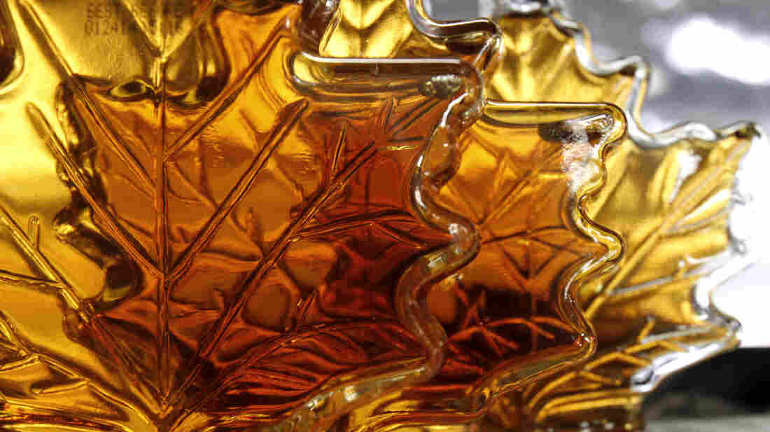 """Maple syrup bottles sit on a shelf. A Canadian syrup producers' federation says a warehouse holding """"over 10 million pounds of maple syrup"""" was recently burglarized."""