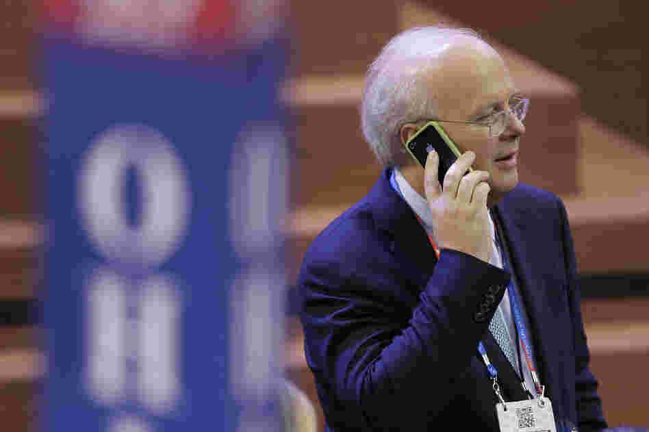 Karl Rove talks on his mobile phone as he walks across the floor before the second session of the Republican National Convention in Tampa on Tuesday.
