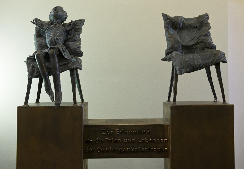 """A sculpture by the artist Bonifatius Stirnberg memorializes the victims of thalidomide, a drug that caused thousands of birth defects. A translation of the German text below the chairs: """"In memory of the dead and the survivors of the thalidomide catastrophe."""" (Jens Schlueter/DAPD via AP)"""