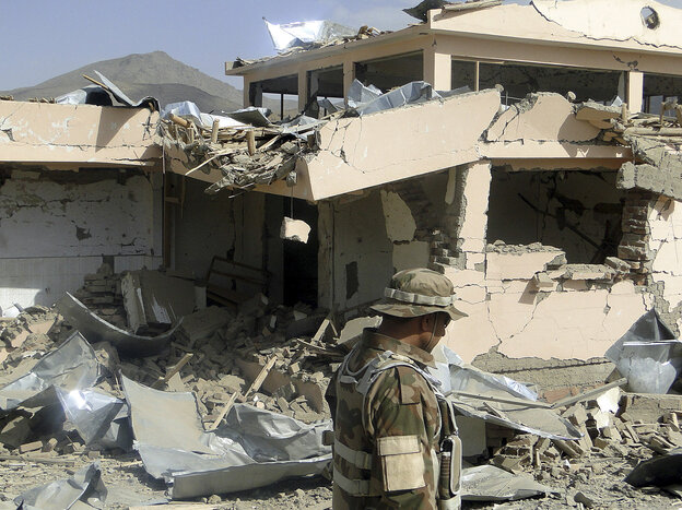 A security official looks at rubble of a building des