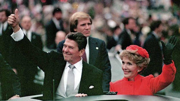 """President Ronald Reagan and his wife, Nancy Reagan, in the inaugural parade in Washington, D.C., in January 1981. In his speech after being sworn in, Reagan called government """"the problem."""" (AP)"""
