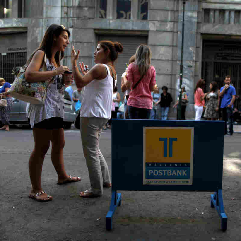 Striking Hellenic Postbank workers chat outside the state-owned bank's headquarters in Athens on Thursday. The union is protesting the government's plan to sell its majority share in the lender.