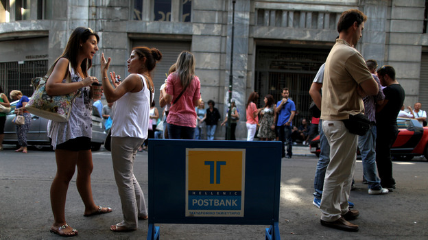 Striking Hellenic Postbank workers chat outside the state-owned bank's headquarters in Athens on Thursday. The union is protesting the government's plan to sell its majority share in the lender. (AP)