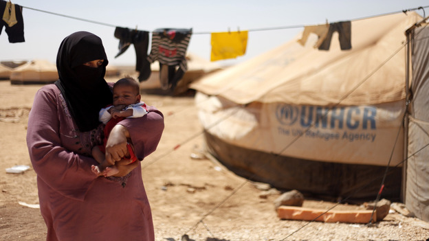 Omm Ahmed, a refugee from Daraa, Syria, carries her infant near her tent at Zaatari Refugee Camp in Mafraq, Jordan, on Sunday. Syrian civilians have borne the greatest brunt of the conflict in their country. (AP)
