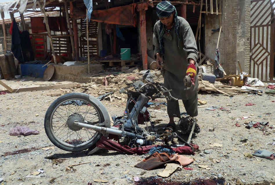 An Afghan man inspects a motorcycle used in a suicide attack in a parking lot holding dozens of trucks supplying the NATO-run Kandahar Air Base in June. Bombings and assassinations are on the rise in Kandahar. Last month, a suicide bomber struck the convoy of the provincial police chief, Gen. Abdul Raziq, who was severely injured.