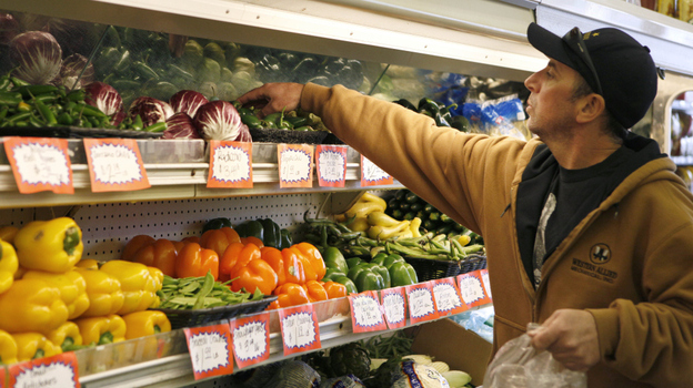A shopper surveys the produce at Pacifica Farmers Market in Pacifica, Calif., in 2011. (AP)