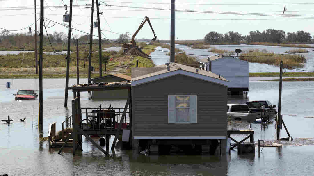 Trucks are flooded in receding flood waters from Hurricane Isaac along Louisiana Hwy 23 near West Point a La Hache, La., in Plaquemines Parish Monday.