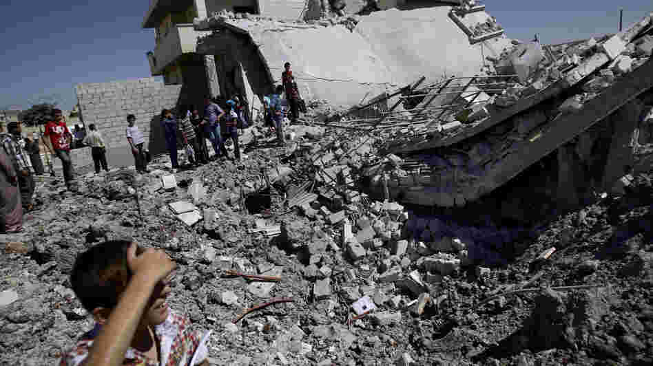 Syrians gather by the rubble of a house destroyed by shelling in the northern town of Azaz, on the outskirts of Aleppo, on Monday.