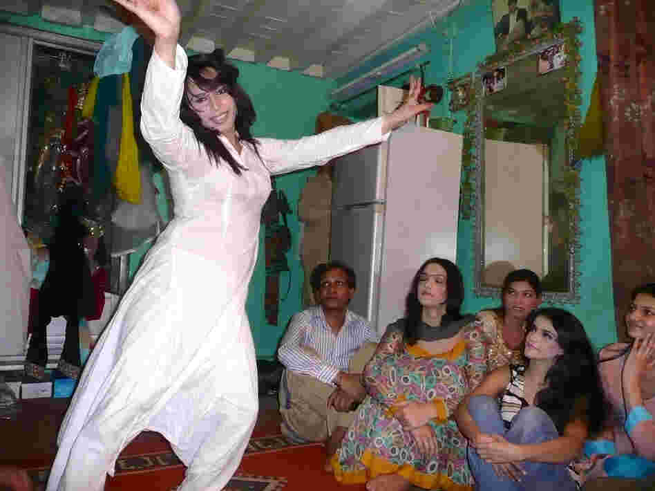 Sameeha, a 22-year-old transgender wedding performer, dances as friends look on during a rehearsal at a friend's home in Rawalpindi.