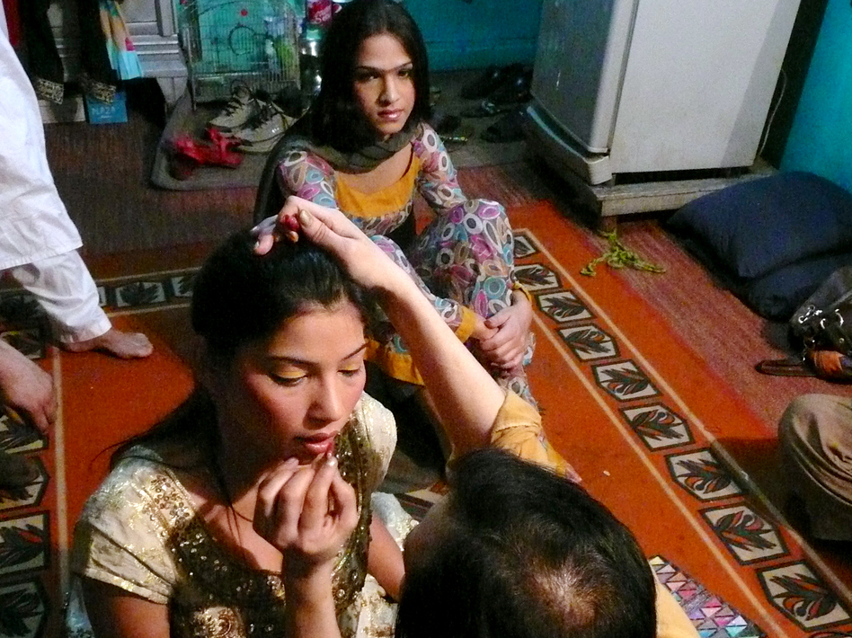 Malaika, 19, sits behind a friend while her makeup is applied at a friend's home in Rawalpindi. The transgender teenager got straight As in school before dropping out because of discrimination from her classmates. Now she dances at weddings and other parties for money. (Lauren Frayer/NPR)