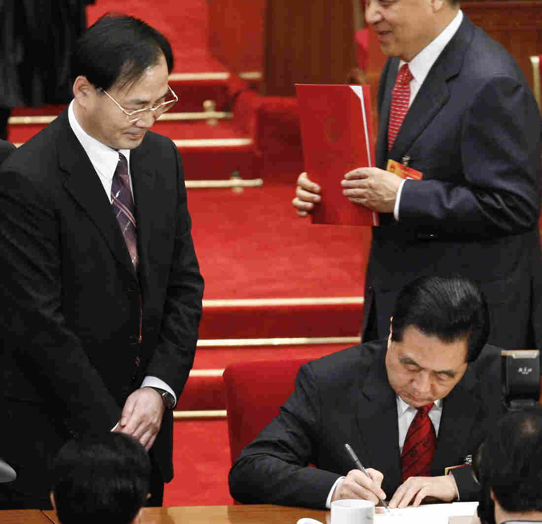 Ling Jihua, left, looked on in March 2010 as Chinese President Hu Jintao, signed a document at the closing ceremony of the National People's Congress in Beijing. Ling has been shifted to a lesser position.