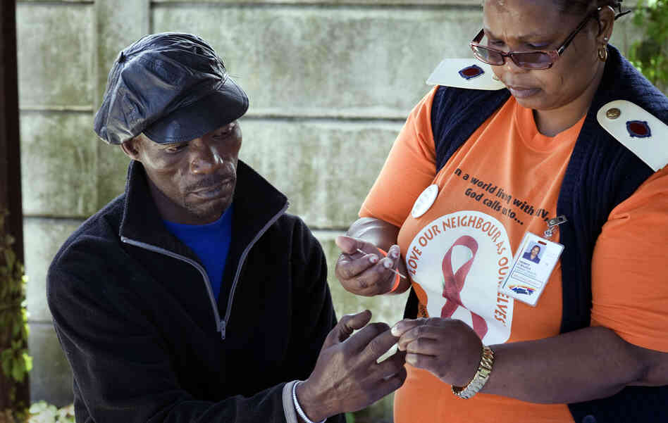 "Nurse Irena Majola tests Justice Mlambo's blood for HIV at a roadside AIDS testing table in a suburb near Cape Town. Under the ""test and treat"" strategy, about 45 million South Africans would need to be screened for HIV each year."