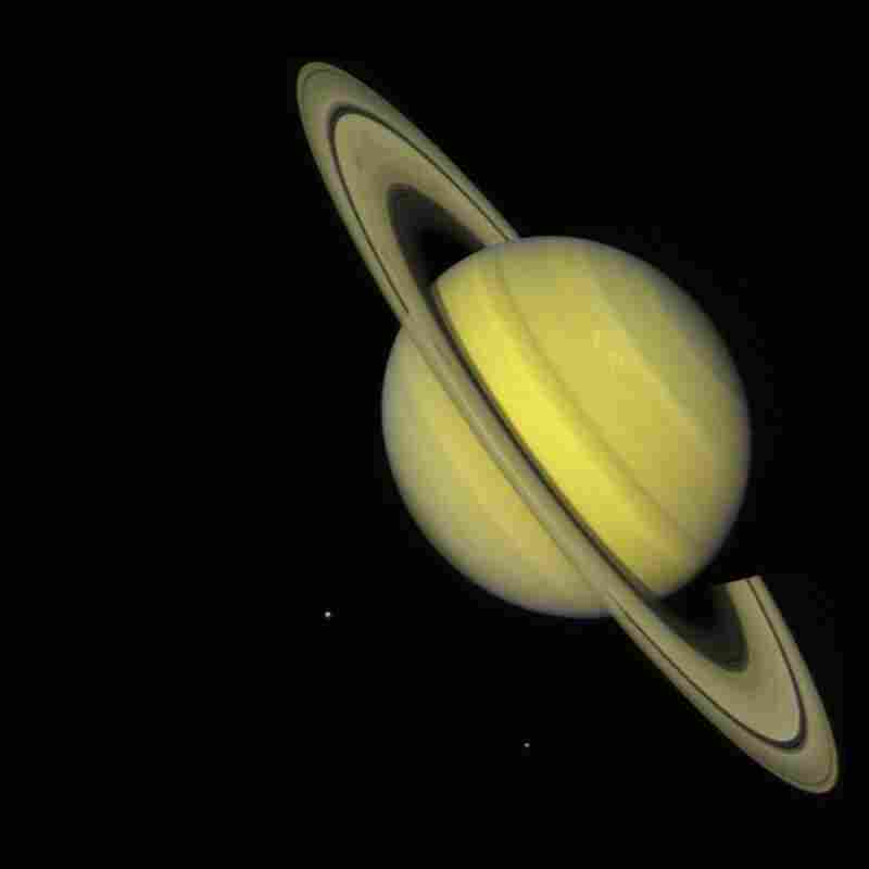 The two Voyager spacecraft launched on Aug. 20, 1977, and Sept. 5, 1977, on a mission to explore Jupiter and Saturn. This true-color image, captured by Voyager 2 on July 21, 1981, shows the moons Dione (small dot at left) and Rhea (lower right) near Saturn.