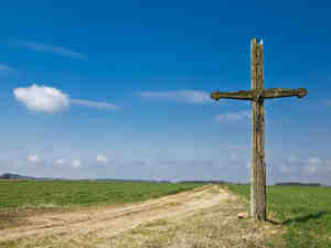 Old wooden cross on a country road.