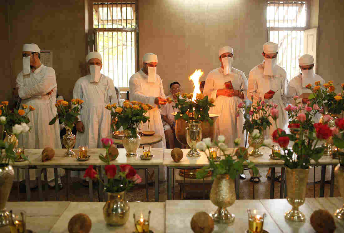 Zoroastrian priests pray to honor the dead inside a temple in Pune, India, on Aug. 18, 2010. Each of the dead is represented by a vase filled with flowers. Parsis forbid images of their funeral ceremonies, where the deceased are taken to the Tower of Silence and consumed by vultures and other birds of prey.