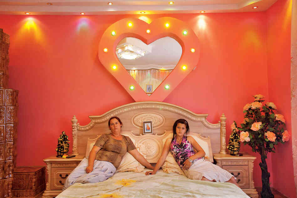 """Buzescu's well-to-do have a thing for flamboyant decor. Vandana Ispilante sits with her 13-year-old daughter, Edera, in a bedroom that looks like a honeymoon suite — except for a picture of the Virgin Mary on the headboard. Odds are Ede"