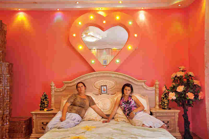 """Buzescu's well-to-do have a thing for flamboyant decor. Vandana Ispilante sits with her 13-year-old daughter, Edera, in a bedroom that looks like a honeymoon suite — except for a picture of the Virgin Mary on the headboard. Odds are Edera's closet will never hold head scarves and long flowered skirts, the traditional Romani dress."""
