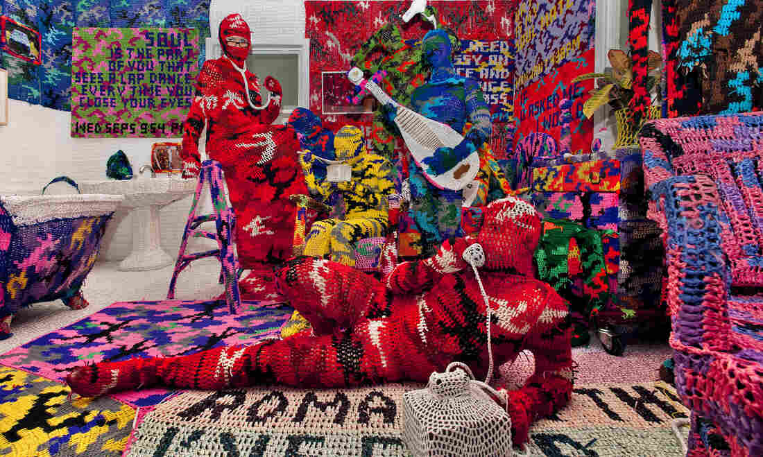 Knitting Is for Pus**** is a work by crochet sculptor Olek. He has created an entire apartment blanketed in brightly colored, crocheted camouflage.