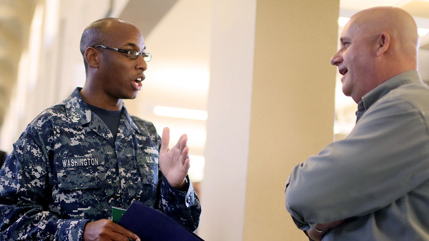 At a job fair in San Diego this week, Navy Sailor E-5 Cedric Washington spoke to Sim Garriotti from Lockheed Martin while interviewing for a potential position. (Getty Images)
