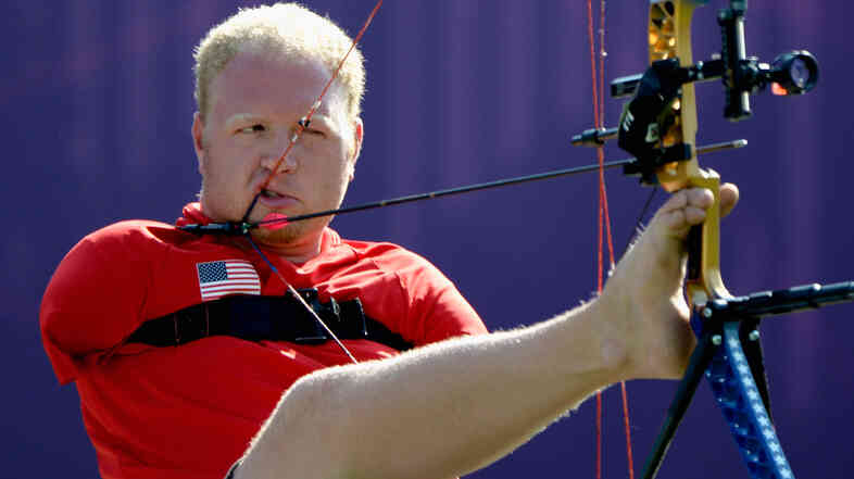 Archer Matt Stutzman of the U.S. prepares to shoot in the London Paralympics. Born without arms, Stutzman uses a release trigger strapped to his shoulder to fire.