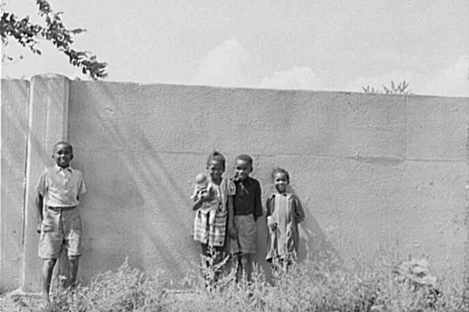 Children stand in front of a half-mile concrete wall in Detroit in 1941. The wall was built in 1940 to separate the black section of the city from a white housing development going up on the other side.
