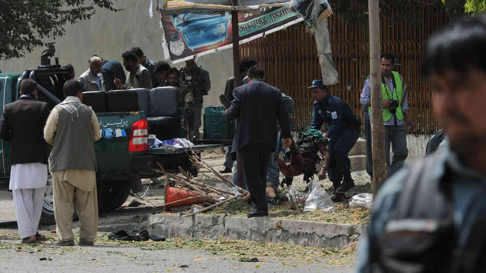 Afghan police carry the remains of a suicide attack victim in the Kabul's diplomatic quarters, home to many Western embassies, on Saturday.