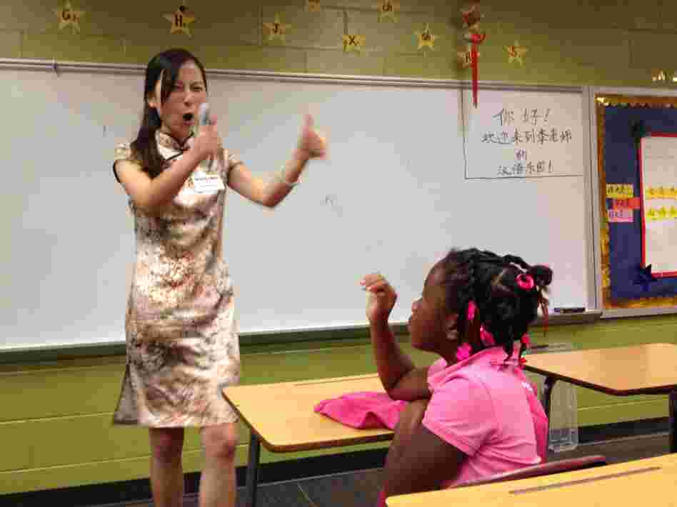 Instructor Huiling Li encourages second-grader Trinity Faulkner on the first day of Mandarin Chinese classes at Brookdale Elementary School in Macon, Ga.