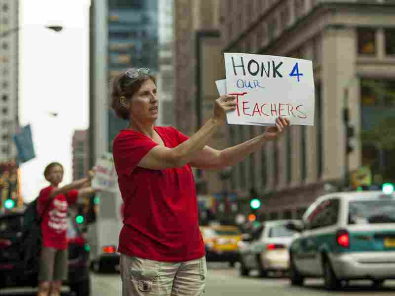 Members of community group Parents 4 Teachers display pro-teacher posters outside City Hall Friday in Chicago. The Chicago Teachers Union has threatened to strike Monday if negotiations fail.