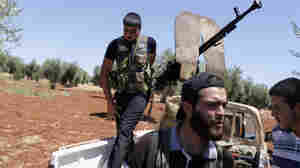Rebel fighters take up position near the military airport outside the rebel-held town of Azaz in northern Syria on Aug. 21. In rebel-held towns like Azaz, activists are taking on new, risky roles as the uprising against Syrian President Bashar Assad continues.