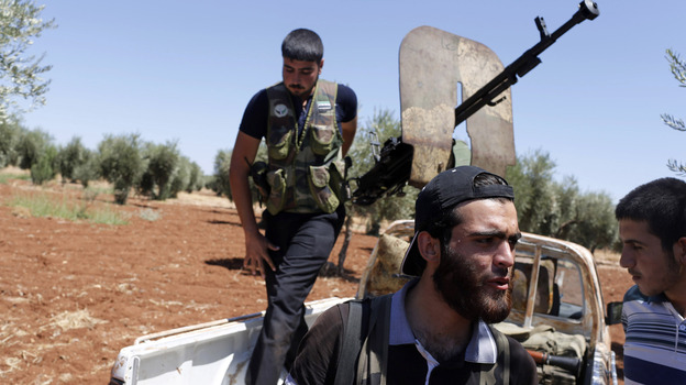 Rebel fighters take up position near the military airport outside the rebel-held town of Azaz in northern Syria on Aug. 21. In rebel-held towns like Azaz, activists are taking on new, risky roles as the uprising against Syrian President Bashar Assad continues. (Reuters/Landov)