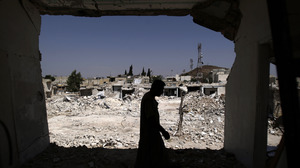 A man walks in his house, which was destroyed in shelling by Syrian government forces, in Azaz, northern Syria. Rebels say the town is under nightly attack.